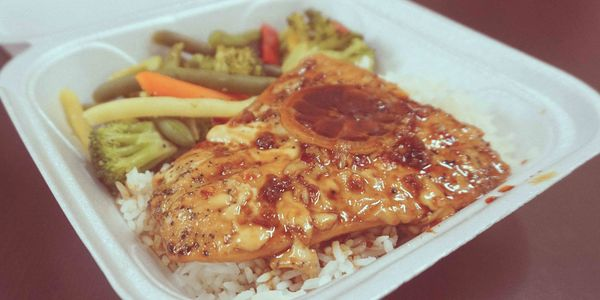 Salmon with lemon and vegetables on a bed of white rice