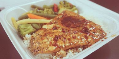 Baked salmon in honey garlic sauce on a plate of white rice with healthy vegetables