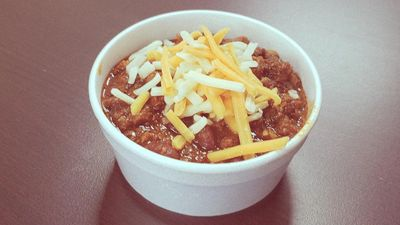 A small bowl of classic chili with white and yellow cheese toppings.