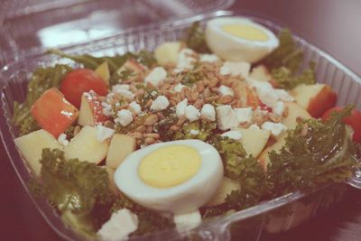 Photograph of salad with eggs, cheese, tomato, lettuce, and garnish.