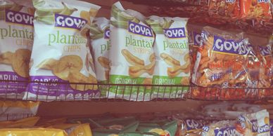 A row of Goya brand plantain chips sitting on a store shelf.