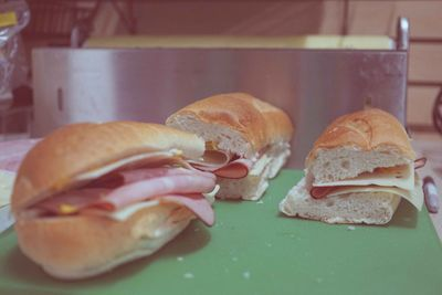Three Cuban sandwiches with ham, pork, cheese pickles and yellow mustard being prepared.