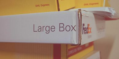 A  stack of FedEx and DHL shipping boxes.