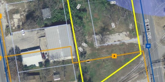 A satellite image of the property. Lot lines and a FEMA flood map overlaid. Empty land is outlined.