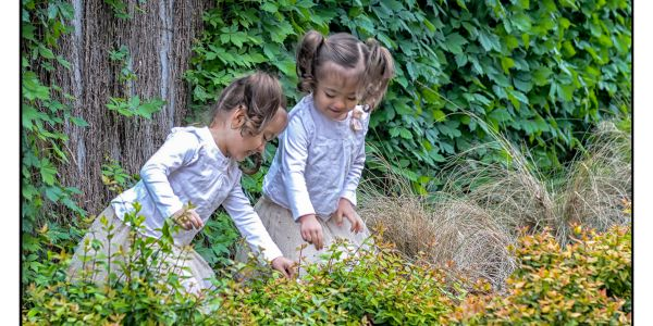 Two twin girls playing with flowers for a great family portrait moment.