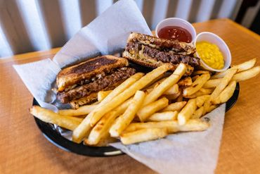 patty melt sandwich in basket with crispy baked fries