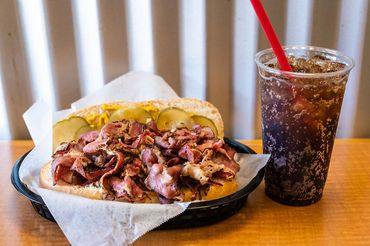 pastrami on french roll sandwich with large Coke