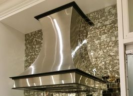 Stainless steel range hood with color matched trim, hand polished.