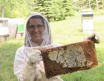 Juliette wearing a full beekeeping suit holding a beehive frame