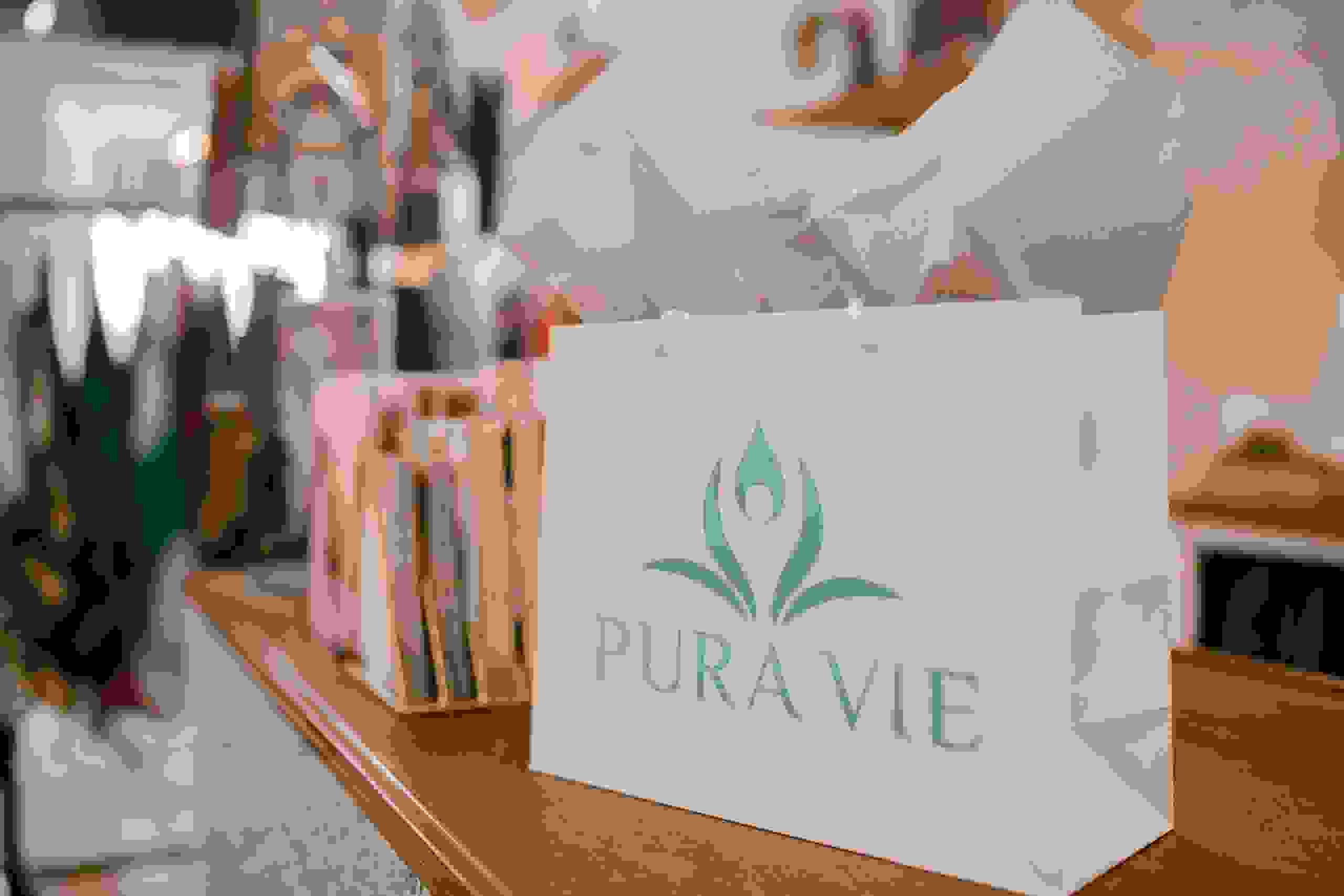 Pura Vie gift bag with tissue paper sitting on top of retail desk with shopping gifts