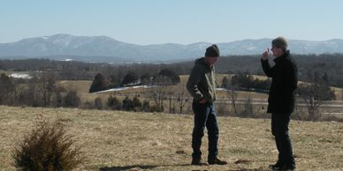 Two men discussing the future of Mount Airy Farm during the winter. Snow is on mountains in distance