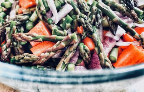 Raw asparagus and red pepper salad in rustic bowl