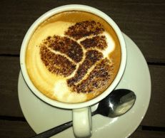 A cup of single origin coffee Ethiopian Yirgachette with cocoa leaf design on top
