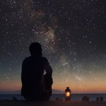 man looking at night sky with later by his side
