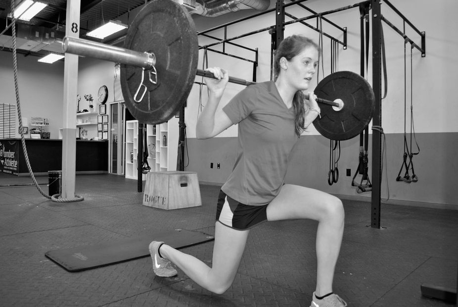 Female Soccer Player doing weighted barbell lunges at Bomber Athlete.