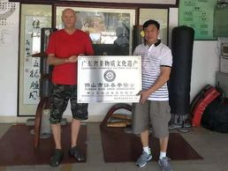 Master Lun Zhixiong presenting Derek Frearson with a plaque.
