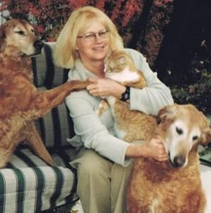 blonde woman sitting down holding gold cat with 2 orange dogs on either side