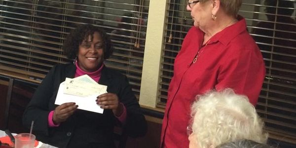 Carolyn Allen presents a check to an Administrator of the Betty Griffin House for battered woman.