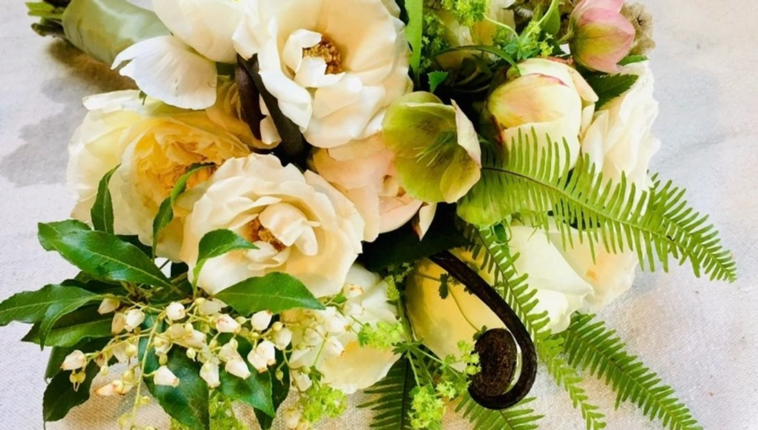 Bridal bouquet of hellebores, piers, garden rose, uhule and umbrella fern and alchimellia.