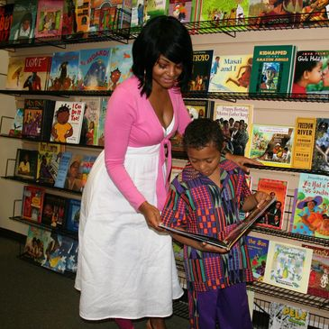 black women and child reading a book in a black book store or african american book store.