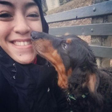 A smiling white woman being nuzzled by a dachshund.