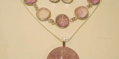 Dried hellebore petals under glass in pendant, bracelet and earrings.