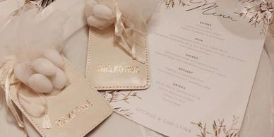 Leather luggage tags, personalised wedding menus, circle seating chart, gold mirror table numbers.