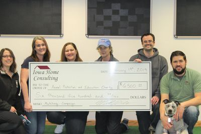 Iowa Home Consulting donation check to low cost spay, neuter, and vaccine clinic