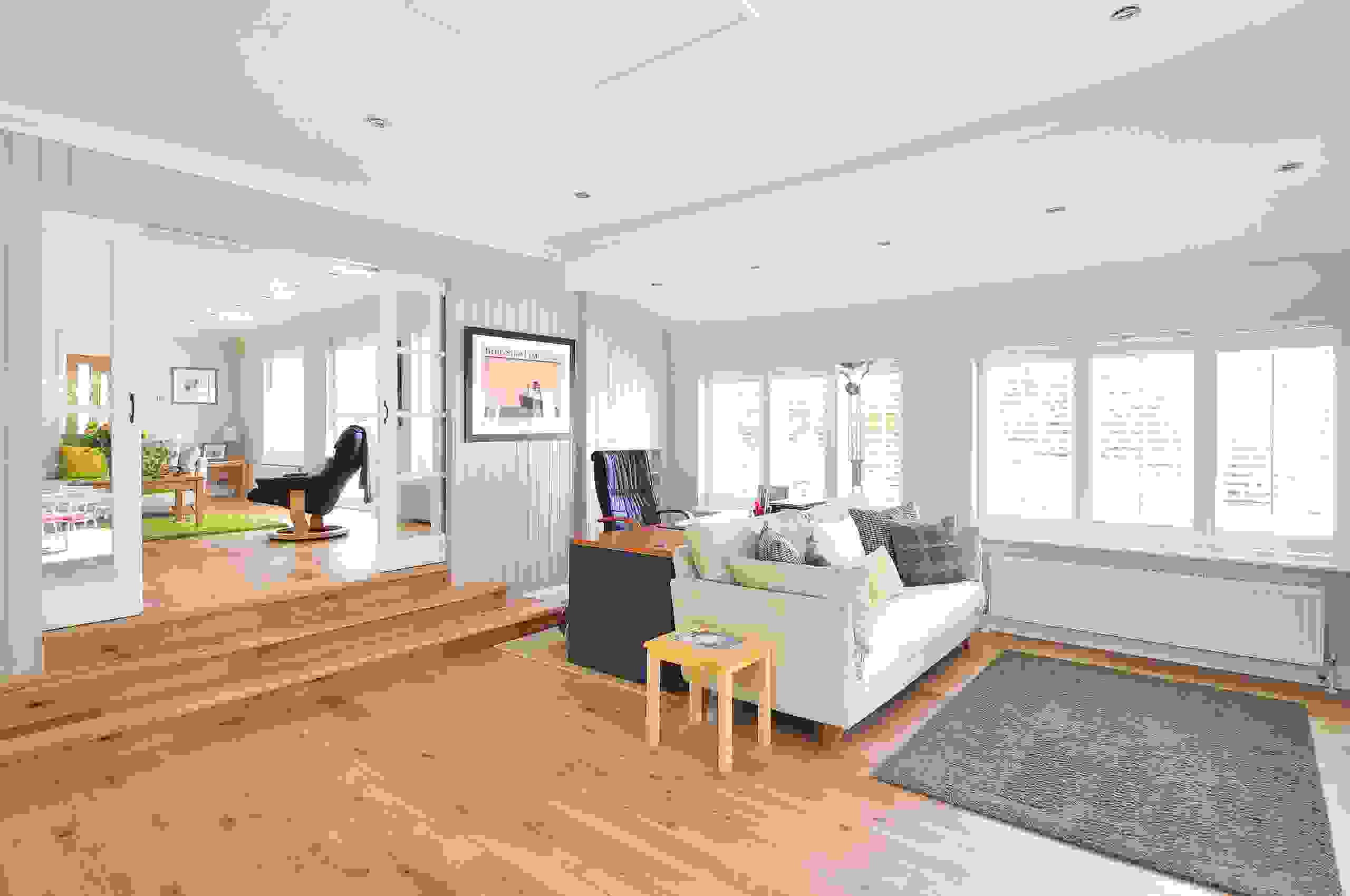 A beautiful living room interior with hard wood flooring and fresh white interior paint