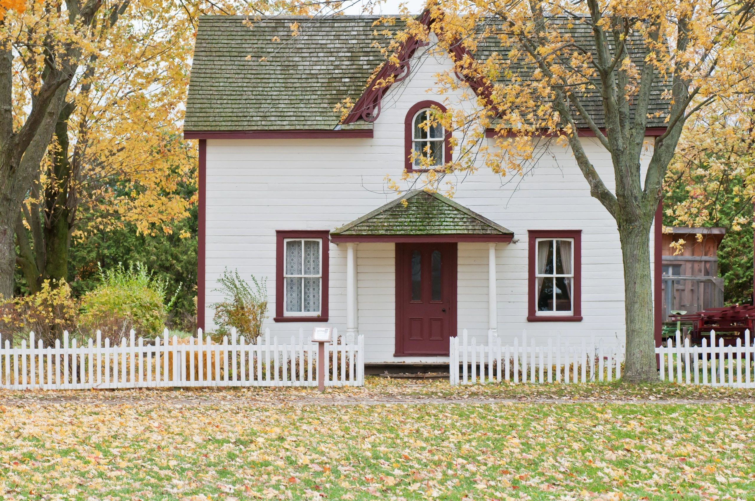 A freshly painted house exterior with white picket fence