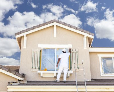 A painter prepping and painting the exterior trim of a house