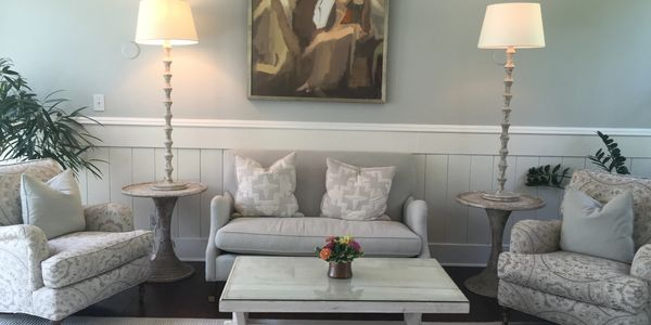 a gray couch, two chairs, a coffee table w/ small flower arrangement, art above the centered couch