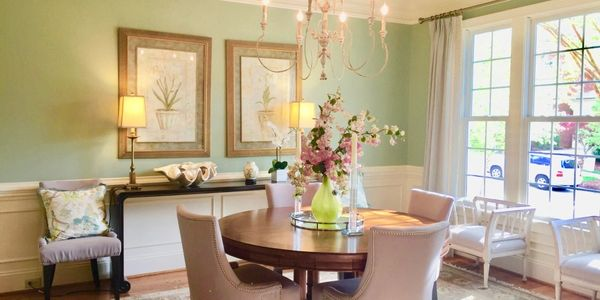 Dining room with round table with a flower arrangement, chairs, green paint on the wall, side table.