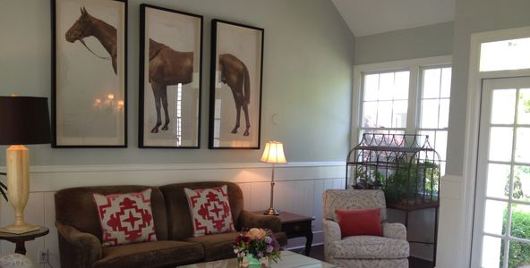Living room couch, red & white pillows, three pictures above show head, middle and end of a horse.