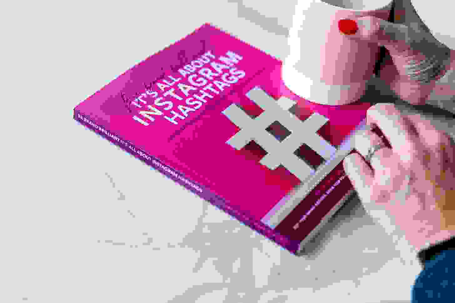 close up of It's all about Instagram hastags book with ladies hand holding a pink mug