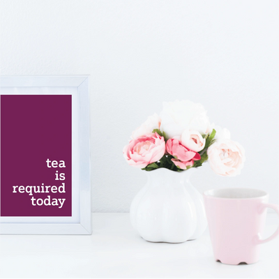 pink mug and vase of flowers on a desk with picture frame with the text tea is required today