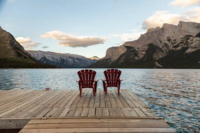 Two red chairs on a dock. Photo by Andre Furtado.