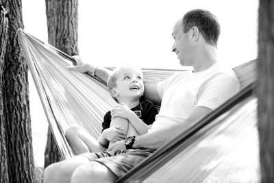 father and son on a hammock in discussion
