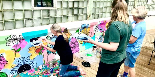 Millhouse artists Dana Brock, Andrea Holmes, Gail Delger, Lisa Temple work on the Millhouse mural