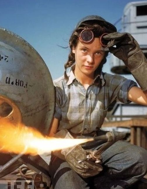 A welder at a boat-and-sub-building yard adjusts her goggles before resuming work, October, 1943.
