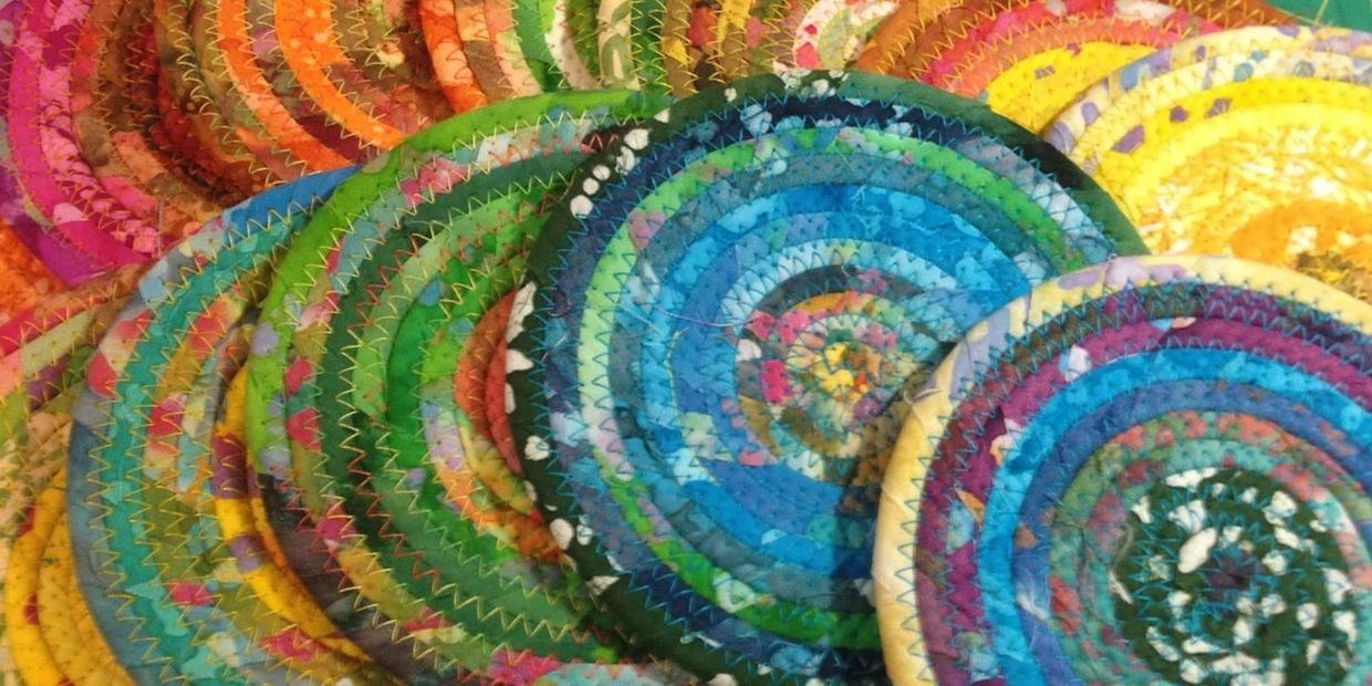 Several of my unique and colorful fabric covered coiled clothesline coasters.