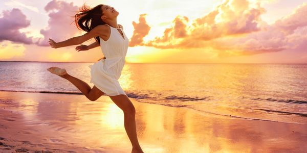 Healthy happy young woman, exuberant, running and jumping on beach at sunset