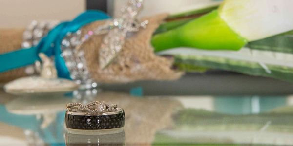 Wedding rings on glass with dragonfly in the background. Alexandria MN Wedding Photographer.