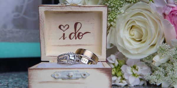 Wedding rings in an 'I do' wooden box with roses on a wedding day at Broadway Ballroom in Alexandria Minnesota by G'Mariecee Portrait Studios.