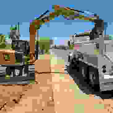 excavating tractor and dump truck