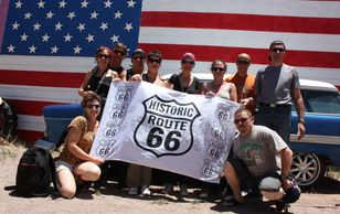 A Route 66 Banner Experience in fron of an American flag mural.