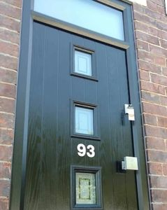 Black Brown composite front door with matching grey frame, square handle and a top light.