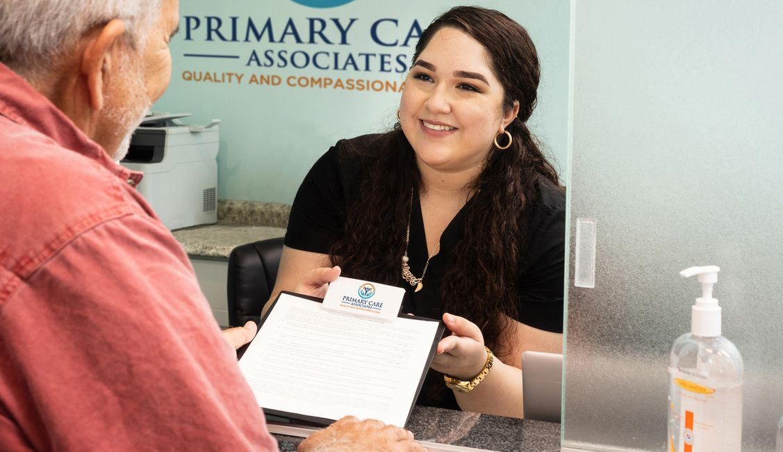 Receptionist hands over patient forms in Primary Care Associates office.