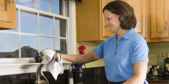 Always Ready Cleaning maid cleaning a kitchen faucet.