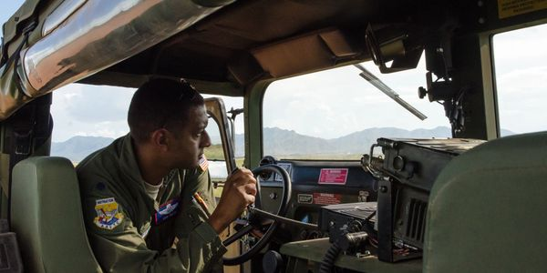 United States Air Force officer, talking on radio in a humvee, during an air drop. AATTC Symposium.